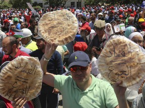"Jordanian protesters shout ""bread"" in front of the Labour Union offices in Amman, Jordan Wednesday, June 6, 2018. ""Corruption equals hunger,"" is written in Arabic on loaves of bread."
