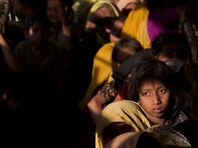 FILE - In this Jan. 27, 2018, file photo, Rohingya refugees wait in a queue to receive relief material at the Balukhali refugee camp near Cox's Bazar, Bangladesh. Myanmar and U.N. agencies signed an agreement that might eventually lead to the return of some of the 700,000 Rohingya Muslims who fled brutal persecution by the country's security forces and are now crowded into makeshift camps in Bangladesh.