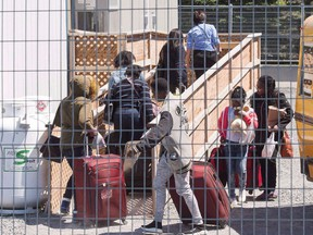A group of asylum seekers arrive at the temporary housing facilities at the border crossing Wednesday May 9, 2018 in St. Bernard-de-Lacolle, Que.