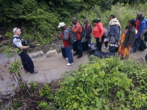 A Royal Canadian Mounted Police officer, left, standing in Saint-Bernard-de-Lacolle, Quebec, advises migrants that they are about to illegally cross from Champlain, N.Y., and will be arrested, Monday, Aug. 7, 2017.