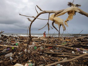 """A Sri Lankan ragpicker searches for plastic waste washed ashore on the promenade of the Indian ocean in Colombo, Sri Lanka, Monday, June 4, 2018. This year's World Environment Day theme, marked on June 5, is """"Beat Plastic Pollution."""""""