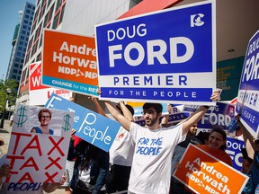 Political supporters rally on May 27, 2018, outside the CBC building in Toronto prior to a leaders' debate for the Ontario election.