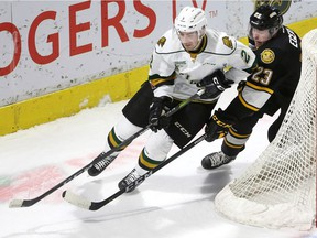 Evan Bouchard lugs the puck out from behind his own net being chased by Sarnia's Curtis Egert in the first period of their Friday December 15, 2017 game at Budweiser Gardens. Mike Hensen/The London Free Press/Postmedia Network