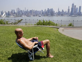 FILE - In this Tuesday, May 15, 2018 file photo, Rick Stewart sits in the sunshine with the New York City skyline in the background, in a park in Weehawken, N.J. According to weather records released on Wednesday, June 6, 2018, May reached a record 65.4 degrees in the continental United States, which is 5.2 degrees above the 20th century average.