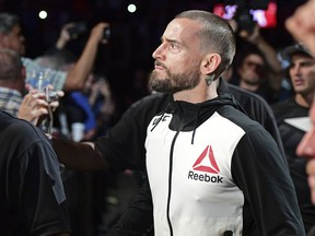 FILE - In this Sept. 10, 2016, file photo, CM Punk walks to the octagon before a welterweight bout at UFC 203 in Cleveland. Jurors have cleared former World Wrestling Entertainment champ CM Punk of defamation and invasion of privacy in a lawsuit brought by a wrestling doctor. Punk, whose real name is Phil Brooks, hugged his wife, former WWE star A.J. Lee., as the panel in Chicago delivered its verdict on Tuesday, June 5, 2018.