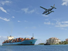 FILE- In this May 5, 2018, file photo, a Tropic Ocean Airways seaplane flies over the container ship Gerd Maersk as the ship heads to Port Miami in Miami Beach, Fla. On Wednesday, June 6, the Labor Department issues revised data on productivity in the first quarter.