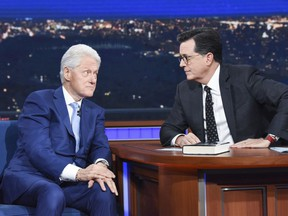 """In this image released by CBS, former President Bill Clinton, left, appears with host Stephen Colbert while promoting his book """"The President is Missing,"""" on """"The Late Show with Stephen Colbert,"""" Tuesday, June 5, 2018 in New York."""