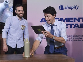 Prime Minister Justin Trudeau uses Shopify's augmented reality technology as Shopify's Daniel Beauchamp, left, looks on in Toronto on Tuesday, May 8, 2018.