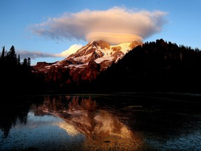 In this September 2012, file photo, a cloud hovers over Mount Rainier at sunset in a view from Klapatche Park Camp at Mount Rainier National Park, Wash.