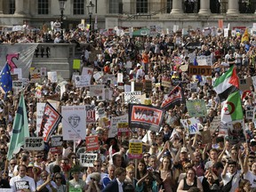 """Protestors holding banners gather after a march opposed to the visit of U.S. President Donald Trump in Trafalgar Square in London, Friday, July 13, 2018. Trump's pomp-filled welcome to Britain was overshadowed Friday by an explosive interview in which he blasted Prime Minister Theresa May, blamed London's mayor for terror attacks against the city and argued that Europe was """"losing its culture"""" because of immigration. In rear is the The National Gallery."""