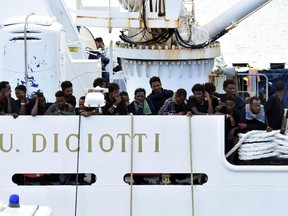 Migrants aboard the Italian Coast Guard ship Diciotti gather on the deck as they await decisions in the port of Catania, Italy, Friday, Aug. 24 2018. An Italian lawmaker says rescued migrants stuck aboard an Italian coast guard ship are starting a hunger strike. Rescued on Aug. 16 in the Mediterranean Sea, 150 migrants are still on the ship after minors and the sick were allowed off in recent days.