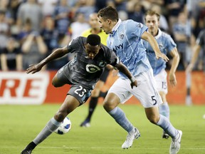 Minnesota United forward Mason Toye (23) loses control of the ball as Sporting Kansas City defender Matt Besler (5) defends during the first half of an MLS soccer match in Kansas City, Kan., Saturday, Aug. 25, 2018.