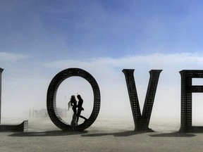 """In this Aug. 30, 2014 photo, a couple stands inside a love sculpture at Burning Man on the Black Rock Desert of Gerlach, Nev. The #MeToo movement is making its way to Burning Man which begins Aug. 26-Sept. 3, 2018. Organizers are reminding attendees that just because the counterculture festival in the Nevada desert is known for occasional nudity and kinky landmarks like the """"Orgy Dome,"""" it doesn't mean it's a free-for-all when it comes to touching or non-consensual sex."""