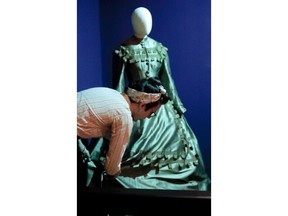 """In this photo made on Thursday, Aug. 23, 2018, Jean-Luc Deladurantaye adjusts one of the dresses while helping to install an exhibit of Ruth E. Carter cinematic costumes at Pittsburgh's Senator John Heinz History Center in Pittsburgh. The exhibit that opens Saturday, Aug. 25, explores Carter's groundbreaking career. """"Heroes & Sheroes: The Art and Influence of Ruth E. Carter in Black Cinema"""" showcases over 40 costumes from nine movies. The costumes include those from """"Amistad,"""" """"What's Love Got to do With It,"""" """"The Butler,"""" """"Malcolm X,"""" """"Selma,"""" """"Do the Right Thing"""" and of course """"Black Panther."""" It is scheduled to run to Dec. 2, 2018."""