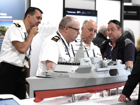People surround a model of a BAE Systems Type 26 Global Combat Ship at the Canadian Association of Defence and Security Industries CANSEC trade show in Ottawa in May 2018.