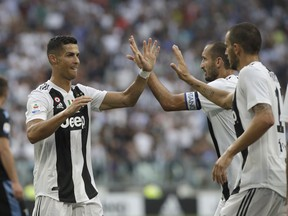 Juventus' Cristiano Ronaldo, left, celebrates with Juventus' Giorgio Chiellini, second right after their teammate Juventus' Miralem Pjanic scored the opening goal of the game during the Serie A soccer match between Juventus and Lazio at the Allianz Stadium in Turin, Italy, Saturday, Aug. 25, 2018.