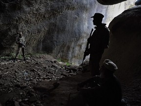 This photo taken on April 26, 2018 shows Pakistani soldiers standing guard at the site of the seventh-century rock sculpture of a seated Buddha carved into a mountain in Jahanabad town in the northwestern Swat Valley of Pakistan, following a restoration process conducted by Italian archaeologists after the Taliban defaced it in 2007.