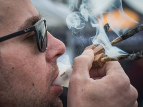Brandon Bartelds smokes three joints at once while attending the 4-20 annual marijuana celebration, in Vancouver, B.C., on Friday April 20, 2018. The Manitoba government has set out fines of up to $2,500 for people who break the rules surrounding cannabis consumption. Once recreational use of the drug is legalized, people who smoke pot in a provincial park or campsite will face a fine of $672, including fees and surcharges.THE CANADIAN PRESS/Darryl Dyck