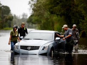 Members of a private critical crisis search and rescue team inspect a vehicle partially submerged in floodwaters during Tropical Storm Florence in Beulaville, North Carolina, U.S., on Sunday, Sept. 16, 2018.
