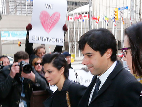 Jian Ghomeshi rushes by protesters during his sex assault trial in Feb. 2016.