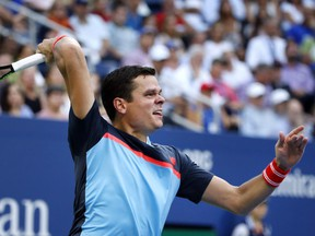 Milos Raonic of Canada returns a shot to John Isner of the United States, during the fourth round of the U.S. Open tennis tournament, Sunday, Sept. 2, 2018, in New York.