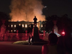 People watch as flames engulf the 200-year-old National Museum of Brazil, in Rio de Janeiro, Brazil, Sunday, Sept. 2, 2018.