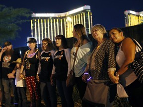 Survivors of a mass shooting form a human chain around the shuttered site of a country music festival on the first anniversary, Monday, Oct. 1, 2018, in Las Vegas.