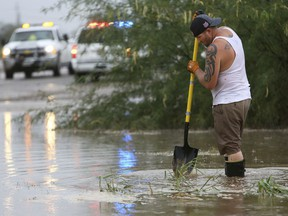 A man tries to dislodge debris from a wash behind homes during rain in Tucson, Ariz., Monday, Oct. 1, 2018. Tropical Storm Rosa soaked northwestern Mexico with heavy rains as it neared the Baja California Peninsula on Monday and was projected to extend into a drenching of the U.S. Southwest.