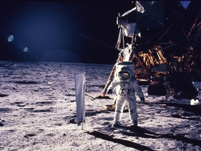 Buzz Aldrin walks on the surface of the moon, with seismographic equipment that he just set up. The flag-like object on a pole is a solar wind experiment and in the background is the Lunar Landing Module. July 20, 1969.