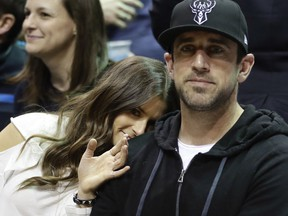 """FILE - In this April 20, 2018 file photo Danica Patrick and Green Bay Packers' Aaron Rodgers watch during the first half of Game 3 of an NBA basketball first-round playoff series between the Milwaukee Bucks and the Boston Celtics in Milwaukee. Patrick encountered some resistance from Rodgers when she wanted to set up a woman cave in the house they share in Green Bay, Wisconsin. The retired racecar driver proposed converting a bedroom into her own space. She says she got """"shut down"""" even though Rodgers has a man cave in the house."""