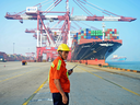 A worker looks on as a cargo ship is loaded at a port in Qingdao, China, in 2017. The new USMCA agreement makes trade talks between Canada and China less likely, experts say.
