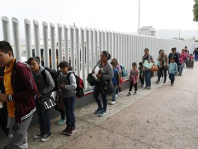 """FILE - This July 26, 2018, file photo shows people lining up to cross into the United States to begin the process of applying for asylum near the San Ysidro port of entry in Tijuana, Mexico. Homeland Security's watchdog says immigration officials were not prepared to manage the consequences of its """"zero tolerance"""" policy at the border this summer that resulted in separation of nearly 3,000 children from parents."""