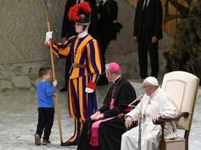 Pope Francis, right, and Prefect of the Papal Household, Georg Ganswein watch a boy who came from the audience onto the stage, play with a Swiss Guard's spear during the weekly general audience on November 28, 2018 at the Vatican.