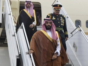 In this photo provided by the G20 Argentina press office, Saudi Arabia's Crown Prince Mohammed bin Salman deplanes at the airport in Buenos Aires, Argentina, Wednesday, Nov. 28, 2018. The prince, who will attend the two-day G20 Summit on Friday and Saturday, was taken to the Saudi embassy in Buenos Aires which is being guarded by dozens of police officers.