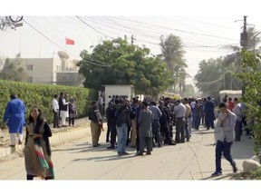 In this image made from video, security officials gather outside the compound of the Chinese Consulate following an attack, Friday, Nov. 23, 2018, in Karachi, Pakistan. Gunmen have stormed the Chinese Consulate in Pakistan's southern port city of Karachi, triggering an intense shootout during which two police officers and all three assailants were killed. (AP Photo)