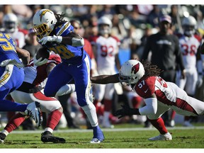 Los Angeles Chargers' Melvin Gordon (28) runs for a touchdown past Arizona Cardinals middle linebacker Josh Bynes (57) during the first half of an NFL football game Sunday, Nov. 25, 2018, in Carson, Calif.
