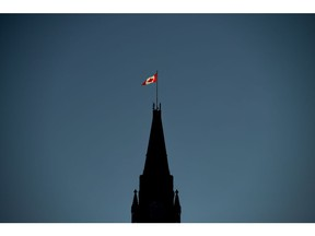 The Canadian Flag is illuminated by morning light atop the Peace Tower on Parliament Hill in Ottawa on Monday, Sept. 17, 2018. Canada is not properly protecting diplomats and staff who face security threats at Canadian missions abroad, including many in locations at high risk of terrorist attacks, violence and espionage, the federal auditor general says.