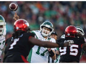 Saskatchewan Roughriders quarterback Zach Collaros, centre, throws the ball as Calgary Stampeders' Ja'Gared Davis, right, closes in during CFL football action in Calgary, Saturday, Oct. 20, 2018. Collaros and the Roughriders return to practice ahead of their CFL West Division semifinal against the Winnipeg Blue Bombers on Sunday.THE CANADIAN PRESS/Jeff McIntosh