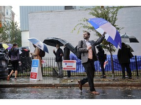 Voters line up in the rain outside Bright Family and Youth Center in the Columbia Heights neighborhood in Washington, Tuesday, Nov. 6, 2018. Across the country, voters headed to the polls Tuesday in one of the most high-profile midterm elections in years.