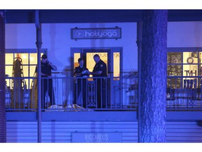 Police investigators work the scene of a shooting, Friday, Nov. 2, 2018, in Tallahassee, Fla.  A shooter killed one person and critically wounded four others at a yoga studio in Florida's capital before killing himself Friday, officials said.