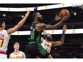 Boston Celtics forward Marcus Morris shoots as guard Jeremy Lin, left, and forward DeAndre' Bembry, right, defend during the first half of an NBA basketball game Friday, Nov. 23, 2018, in Atlanta.