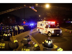 Police and firefighters salute as an ambulance arrives at the medical examiner's office carrying the body of Chicago Police Department Officer Samuel Jimenez, who was killed during a shooting at Mercy Hospital earlier in the day, Monday, Nov. 19, 2018, in Chicago.