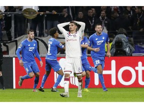 Lyon midfielder Houssem Aouar, center, reacts as Hoffenheim players celebrate their side's 2nd goal during a Champions League group F soccer match between Lyon and Offenheim in Decines, near Lyon, central France, Wednesday, Nov. 7, 2018.