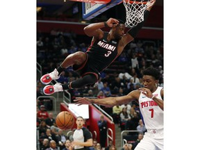 Detroit Pistons forward Stanley Johnson (7) reaches for the ball after a dunk by Miami Heat guard Dwyane Wade during the second half of an NBA basketball game, Monday, Nov. 5, 2018, in Detroit.
