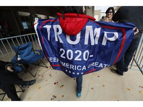 """Eva Sara Landau of Diamondhead, Miss., shows off her """"Trump 2020"""" banner cape as she waits admittance to the rally with President Donald Trump, Monday, Nov. 26, 2018, in Biloxi, Miss. Landau and others braved a cold morning to be the first in line to enter the Mississippi Coast Coliseum."""