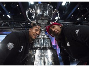 Calgary Stampeders defensive back Patrick Levels, left, and Stampeders wide receiver Bakari Grant, right, eye up the Grey Cup during media day ahead of the106th Grey Cup in Edmonton on Thursday, November 22, 2018.