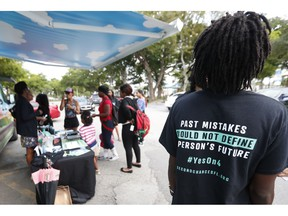 """FILE - In this Oct. 22, 2018 file photo, people gather around the Ben & Jerry's """"Yes on 4"""" truck as they learn about Amendment 4 and eat free ice cream at Charles Hadley Park in Miami.  With a single vote Tuesday, Nov. 6, Florida added 1.4 million possible voters to the rolls when it passed Amendment 4, which said that most felons will automatically have their voting rights restored when they complete their sentences and probation."""