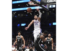 Philadelphia 76ers guard Ben Simmons (25) dunks over Brooklyn Nets forward Rondae Hollis-Jefferson (24) as Nets center Jarrett Allen (31) and guard Spencer Dinwiddie (8) look on during the first half of an NBA basketball game, Sunday, Nov. 4, 2018, in New York.