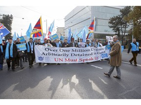 Uyghurs and Tibetan people demonstrate against China during the Universal Periodic Review of China by the Human Rights Council, walking to the place des Nations in front of the European headquarters of the United Nations, in Geneva, Switzerland, Tuesday, Nov. 6, 2018.