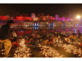 Devotees light earthen lamps on the banks of the River Sarayu as part of Diwali, the Hindu festival of lights celebrations in Ayodhya, India, India, Tuesday, Nov. 6, 2018. The northern Indian city of Ayodhya has broken a Guinness World Record after lighting 300,150 earthen lamps and keeping them lit for at least 45 minutes.